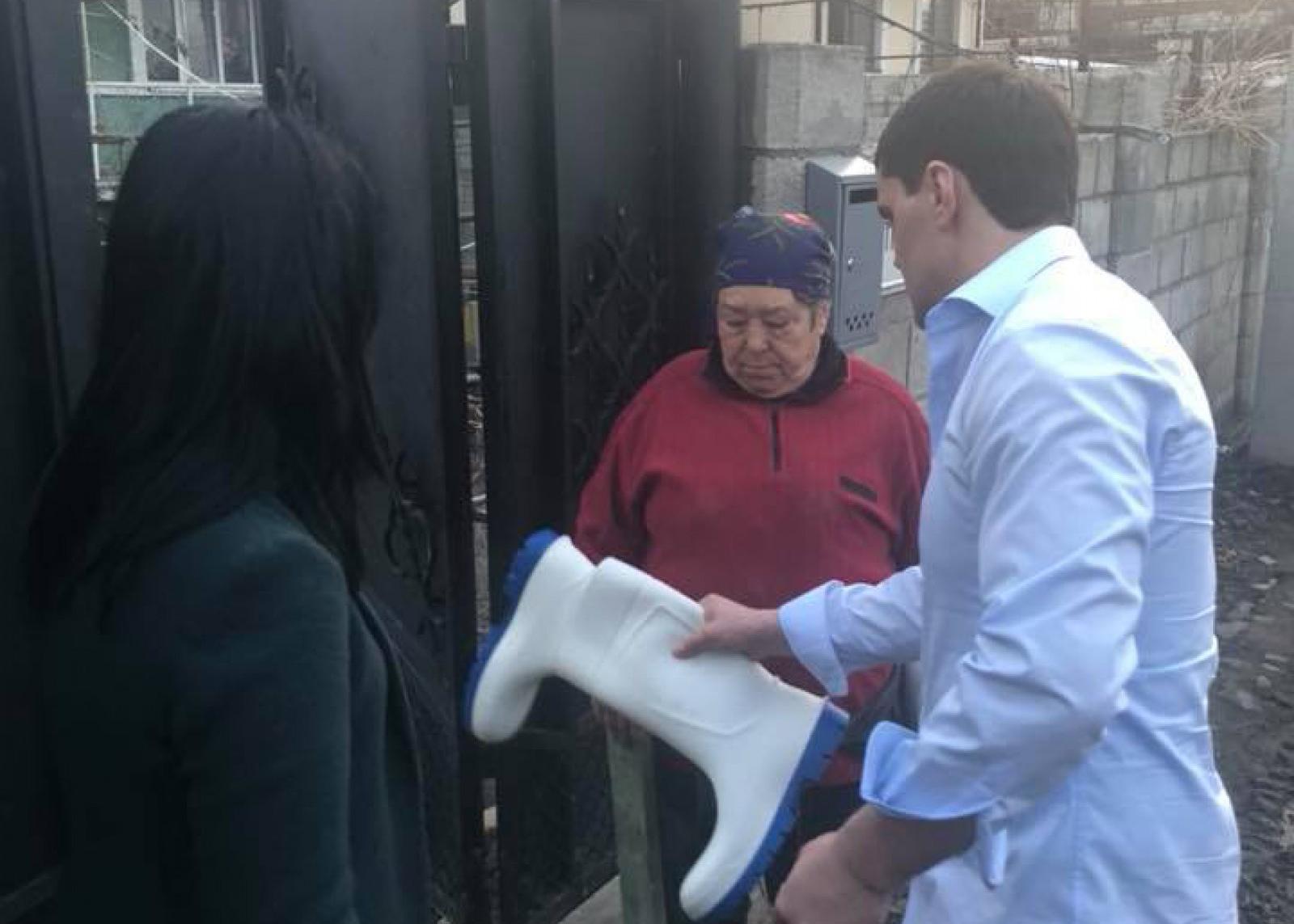 Imaginea zilei: După cum e drumul, așa și darurile. Constantin Țuțu a oferit mai multor familii din Trușeni și Durlești cizme de cauciuc