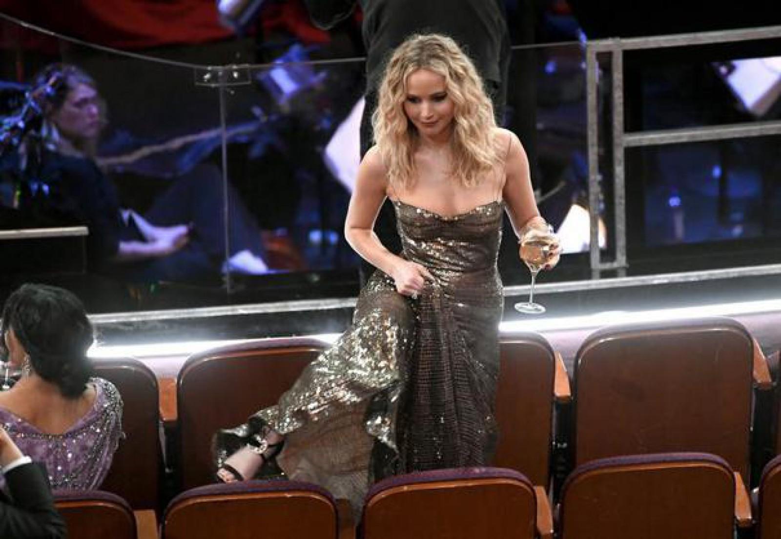Stop cadru la Oscar 2018: Escalada lui Jennifer Lawrence în căutarea locului său. Actriţa, îmbrăcată într-o rochie lungă, purta tocuri înalte şi avea un pahar de vin în mână