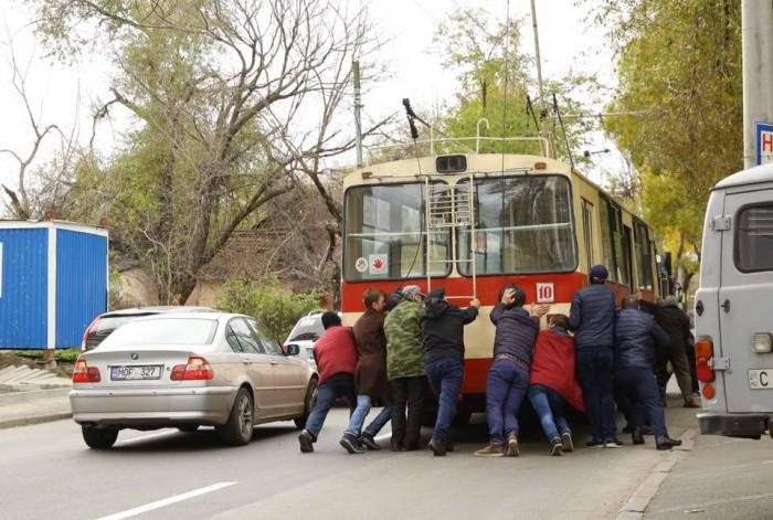 (imaginea zilei) Călători, surprinși pe o stradă cum împing un troleibuz de pe ruta 10